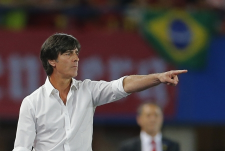 Germany's national football team head coach Joachim Low gestures as a Brazilian flag is seen in the background during a 2014 World Cup qualification football match between Germany and Austria on September 11, 2012, at the Ernst Happel Stadium, in Vienna. Germany won 2-1. AFP PHOTO / ALEXANDER KLEIN