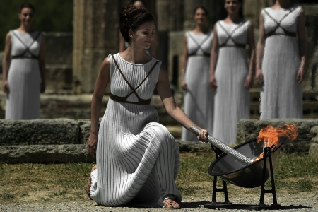Actress Katerina Lechou performing as the high priestess lights the Olympic flame at the Temple of Hera  on April 21, 2016 during the lighting ceremony of the Olympic flame in ancient Olympia, the sanctuary where the Olympic Games were born in 776 BC.  The Olympic flame was lit today and solemnly sent off carrying international hopes that Brazil's political paralysis will not taint the Rio Games that start in barely 100 days. / AFP PHOTO / ARIS MESSINIS